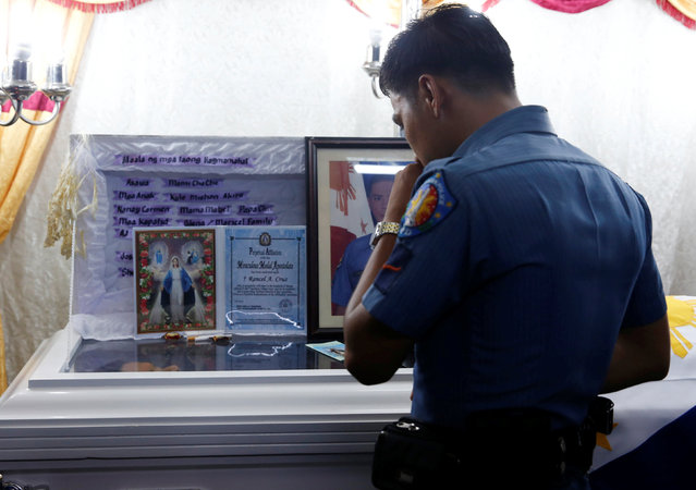 A policeman pays his respects to fellow officer Rancel Cruz, whom police investigators said was shot dead by a drug addict, in Manila, Philippines October 19, 2016. (Photo by Erik De Castro/Reuters)