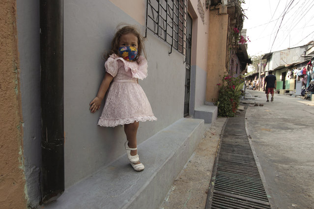 Five-year-old Fernanda Serrato poses in front of her house wearing a homemade mask to protect her from the spread of the new coronavirus, in the Papini community of San Salvador, El Salvador, Thursday, April 23, 2020. When the coronavirus appeared, President Nayib Bukele closed the borders and airports and imposed a mandatory home quarantine for all except those working in the government, hospitals, pharmacies or other designated businesses. People were allowed out only to buy groceries, and violators were detained, with more than 2,000 being held for 30-day stints. (Photo by Salvador Melendez/AP Photo)