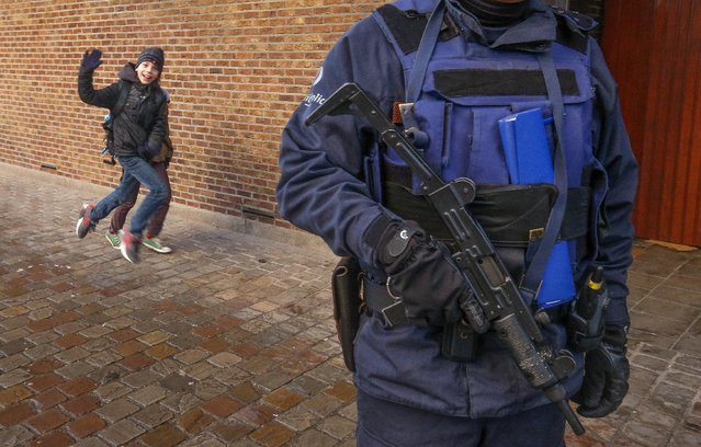 A Belgian police officer stands guard outside a school in central Brussels November 25, 2015. Brussels' schools re-opened on Wednesday after staying closed for two days following tight security measures linked to the fatal attacks in Paris. (Photo by Yves Herman/Reuters)