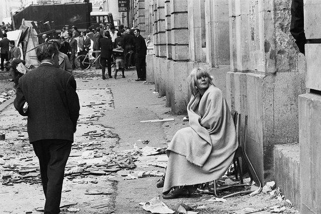 A woman sits in a chair on Rue des Saints Peres, near l'Ecole de Medecine, the day after student clashes with police in the Latin Quarter of Paris, France, May 11, 1968. (Photo by Gökşin Sipahioğlu/SIPA Press)