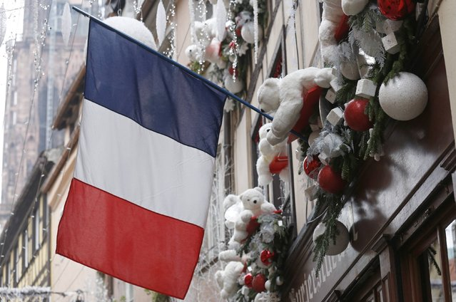 A French flag hangs from a window of a restaurant decorated for Christmas holiday season in Strasbourg, France, November 27, 2015 after the French President called on all French citizens to hang the tricolour national flag from their windows to pay tribute to the victims of the Paris attacks during a national day of homage. (Photo by Vincent Kessler/Reuters)