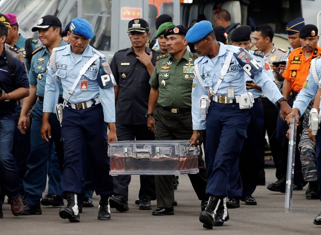 Indonesian air force personnel carry the flight data recorder of the ill-fated AirAsia Flight 8501 that crashed in the Java Sea, at airport  in Pangkalan Bun, Indonesia, Monday, January 12, 2015. Divers retrieved one black box Monday and located the other from the AirAsia plane that crashed more than two weeks ago, a key development that should help investigators unravel what caused the aircraft to plummet into the Java Sea. (Photo by Achmad Ibrahim/AP Photo)
