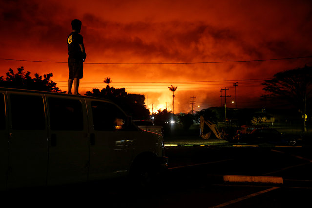 Darryl Sumiki, 52, of Hilo, watches as lava lights up the sky above Pahoa during ongoing eruptions of the Kilauea Volcano in Hawaii, U.S., June 2, 2018. (Photo by Terray Sylvester/Reuters)