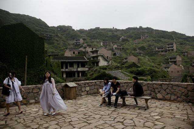 In this May 19, 2018, photo, tourists rest inside the abandoned fishing village of Houtouwan on the remote island of Shengshan, 90 kilometers off the coast of Shanghai. (Photo by Sam McNeil/AP Photo)