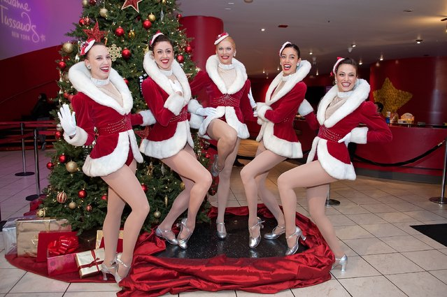 The Radio City Rockettes pose with a Radio City Rockette wax figure at Madame Tussauds on December 3, 2015 in New York City. (Photo by D Dipasupil/Getty Images)