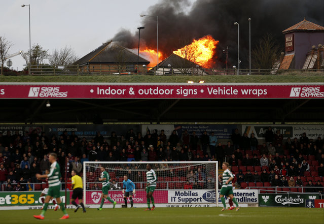 Fire rages at the near by Sixfields Tavern as play continues during the FA Cup second round match between Northampton and Norwich Victoria at Sixfields Stadium, Northampton, central England, Saturday December 5, 2015. (Photo by Paul Harding/PA Wire via AP Photo)
