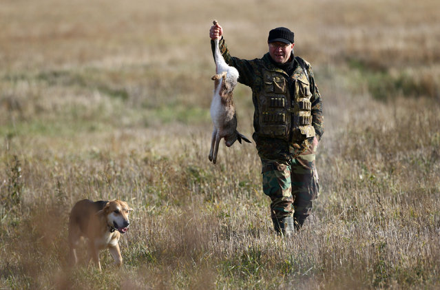 A hunter carries a hare he just killed during a hunt in a field near the village of Novosyolki, Belarus November 5, 2016. (Photo by Vasily Fedosenko/Reuters)