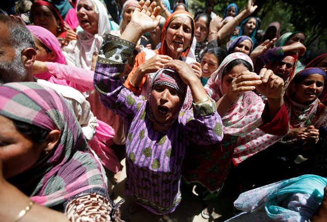 Relatives mourn as they watch the body of Ghulam Hassan Wagay, a policeman who according to local media was killed in a militant attack in south Kashmir's Pulwama district on Monday night, during his funeral at Wohlutra village in north Kashmir's Baramulla district, June 12, 2018. (Photo by Danish Ismail/Reuters)