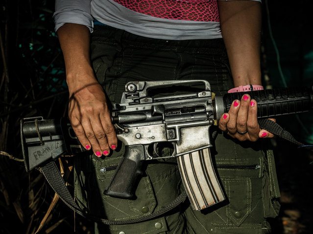Tatiaya Saens, 23, holds an Armalite AR15 rifle in her hands, she has been with Farc for 10 years. She was born in the countryside where the guerrilla movement had a strong presence. She never knew her father, her mother left her when she was just nine months old, so she grew up in the mother's cousins' house where she wasn't treated well. By joining the guerrilla she eyed an opportunity for a better and more secure future, she says. (Photo by Mads Nissen/Politiken/The Guardian/Panos Pictures)