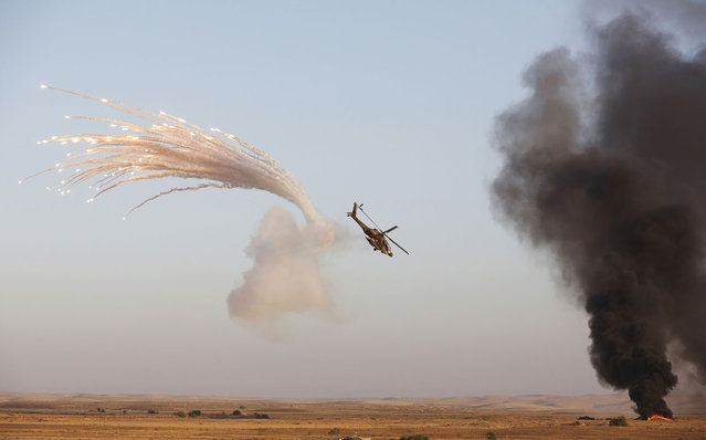 An Israeli Apache helicopter releases flares after it fired at targets (R) during the air force pilots' graduation ceremony at Hatzerim air base in southern Israel June 27, 2013. Some 30 cadets graduated on Thursday where they were also addressed by Israel's Prime Minister Benjamin Netanyahu. (Photo by Baz Ratner/Reuters)