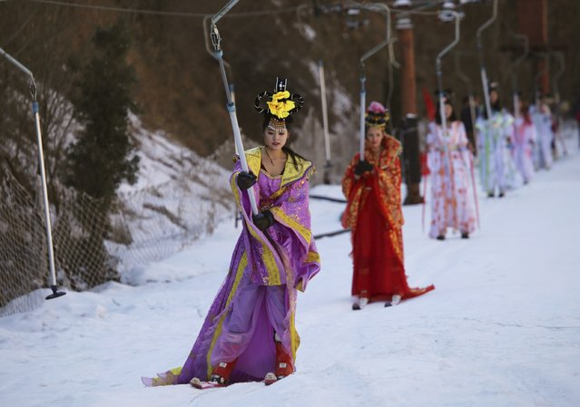 Women dressed in Chinese traditional costumes hold onto a ski lift as they are transferred to top of a ski trail during a promotional event at a ski resort in Sanmenxia, Henan province, January 21, 2015. (Photo by Reuters/Stringer)