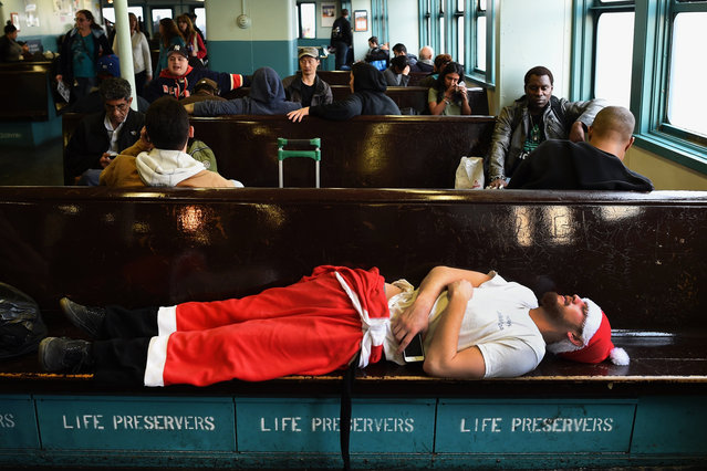 A man dressed in a Santa outfit sleeps on the Staten Island during the SantaCon in New York City on December 12, 2015. (Photo by Timothy A. Clary/AFP Photo)