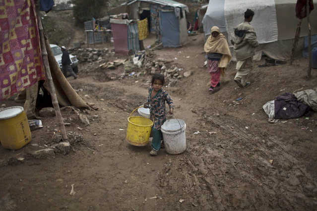 A Pakistani girl carrying buckets walks back to her family's makeshift tent in a slum in Rawalpindi, Pakistan, Friday, January 23, 2015. (Photo by Muhammed Muheisen/AP Photo)