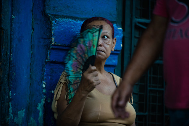 A street vendor fans herself as she sits on the sidewalk in the early morning shuffle in Havana, Cuba on August 4, 2015. (Photo by Sarah L. Voisin/The Washington Post)