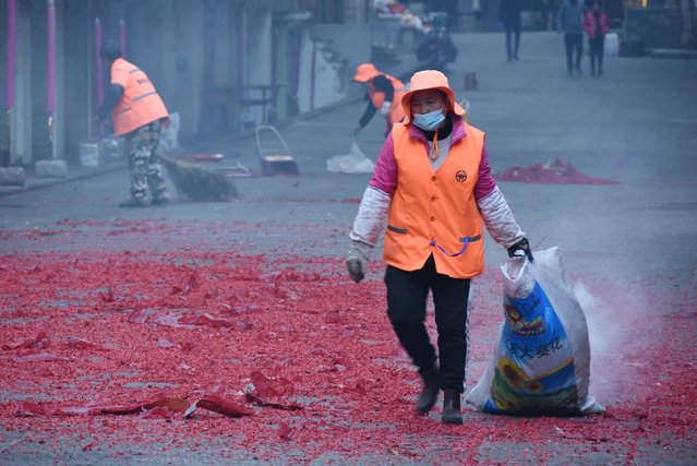 Cleaning workers sweep the trash left behind by revelers after fireworks in southwest China's Yunnan Province, February 11, 2021. (Photo by CFP/China Stringer Network)