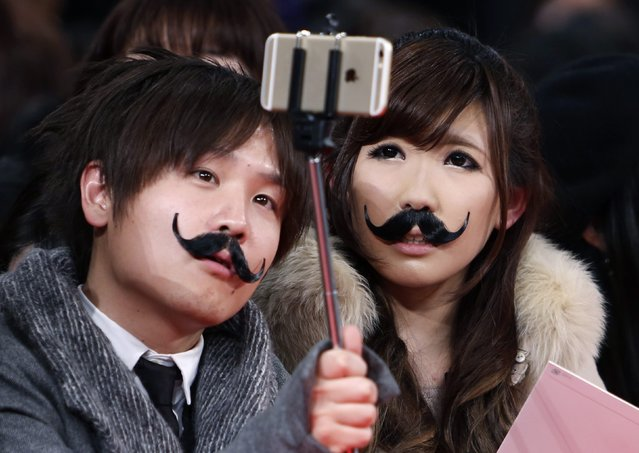 """People wearing fake moustaches take a selfie as they wait for the Japan premiere of """"Mortdecai"""" in Tokyo January 27, 2015. (Photo by Yuya Shino/Reuters)"""
