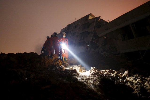 Firefighters use flashlights to search for survivors among the rubble of collapsed buildings after a landslide hit an industrial park in Shenzhen, Guangdong province, China December 20, 2015. (Photo by Tyrone Siu/Reuters)