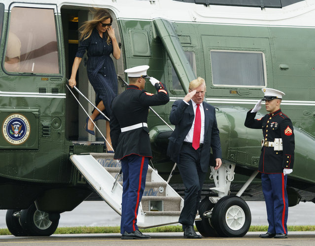 President Donald Trump and first lady Melania Trump walk from Marine One to board Air Force One at Morristown Municipal Airport, in Morristown, N.J., Sunday, July 22, 2018, en route to Washington after staying at Trump National Golf Club in Bedminster, N.J. (Photo by Carolyn Kaster/AP Photo)