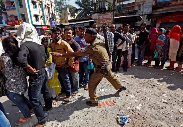 A policeman tries to control the crowd outside a bank as people queue to deposit or exchange their old high denomination banknotes in Siliguri, India, November 16, 2016. (Photo by Rupak De Chowdhuri/Reuters)