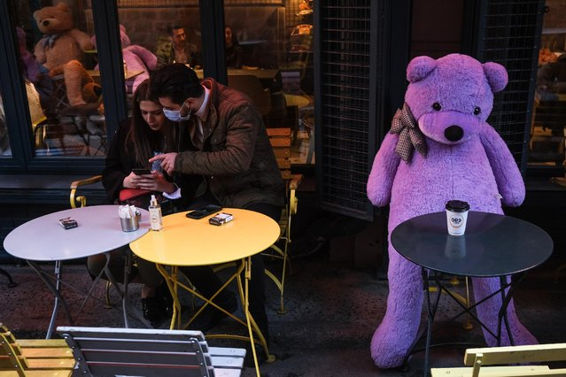 A couple enjoy their time next to a teddy bear at a cafe in Istanbul, Turkey, 09 March 2021. Turkish restaurants and cafes have reopened after three months of closure and many children returned to schools on 09 March after the government announced steps to ease COVID-19 curbs even as cases grow higher, raising concerns in the top medical associations. (Photo by Sedat Suna/EPA/EFE)