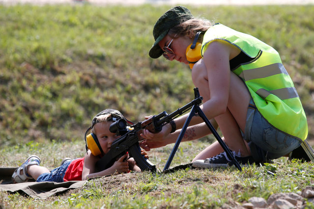 An instructor teaches a boy to shoot a Kalashnikov machine gun during the International Army Games 2018, in Alabino, outside Moscow, Russia on July 28, 2018. (Photo by Sergei Karpukhin/Reuters)