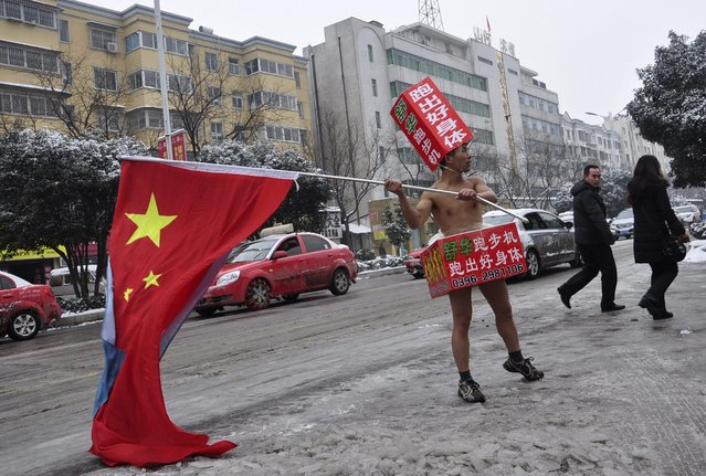 Pedestrians look on as a topless man (C), carrying a Chinese national flag and wearing cardboards printed with advertisements, promotes exercise equipment on a street covered by thin snow in Zhumadian, Henan province January 29, 2015. (Photo by Reuters/Stringer)