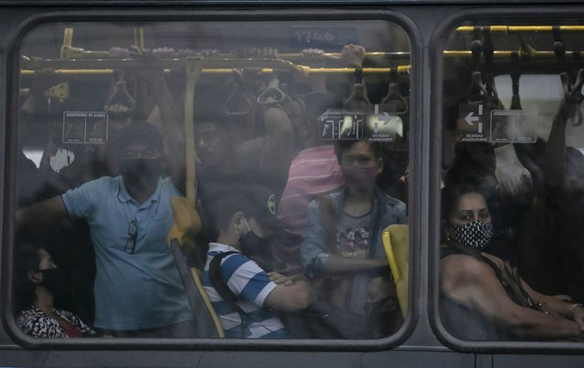 Commuters wearing masks due to the COVID-19 pandemic crowd a public Rapid Transit Bus (BRT) in Rio de Janeiro, Brazil, Tuesday, March 30, 2021. (Photo by Bruna Prado/AP Photo)