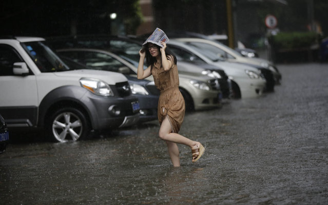 A woman walks on the flooded street from a heavy thunderstorm in Shanghai, China, Friday, September 13, 2013. Sudden and heavy thunderstorm hit the city in the afternoon Shanghai and caused the flood with rain water over many streets. (Photo by Eugene Hoshiko/AP Photo)