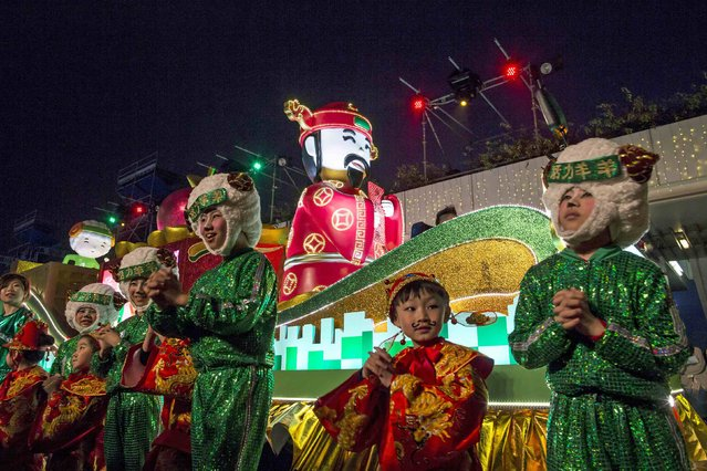 Performers dressed as the Wealth of God and Sheep during a Chinese New Year evening parade at Hong Kong's Tsim Sha Tsui shopping district February 19, 2015. (Photo by Tyrone Siu/Reuters)