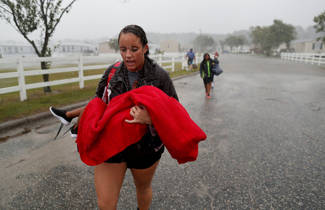 During a driving rain, Maggie Belgie of The Cajun Navy, carries a child evacuating a flooding trailer community during Hurricane Florence in Lumberton, North Carolina, U.S. September 15, 2018. (Photo by Randall Hil/Reuters)