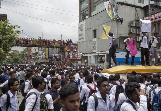 Bangladeshi students shout slogans as they block a road during a protest in Dhaka, Bangladesh, Wednesday, August 1, 2018. Students blocked several main streets in the capital, protesting the death of two college students in a bus accident in Dhaka. (Photo by A. M. Ahad/AP Photo)