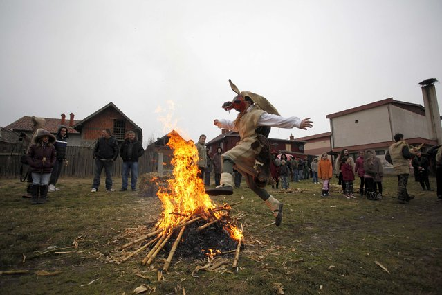 A boy wearing a mask jumps over a fire during Bele Poklade carnival celebrations in the village of Lozovik, some 100 km (62 miles) from the capital Belgrade, February 22, 2015. Bele Poklade has its roots in old pagan customs and is marked annually seven weeks before Easter. Children walk through the village to collect eggs, and at the end they jump over a fire to banish evil demons. (Photo by Djordje Kojadinovic/Reuters)
