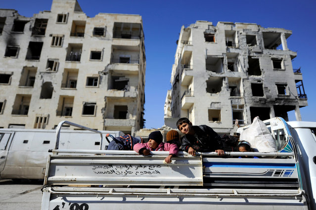Children that came back with their families to check their homes ride a pick-up truck near damaged buildings in goverment controlled Hanono housing district in Aleppo, Syria December 4, 2016. (Photo by Omar Sanadiki/Reuters)