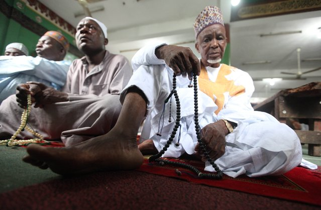 Nigeria Muslims offer prayers during Eid al-Adha prayers to mark the end of the holy month of Hajji in Lagos, Nigeria, Tuesday, October 15, 2013. Traditionally Muslims all over the world slaughter cattle and goats and distribute the meat to the needy, during the Eid al-Adha festival which honors the prophet Abraham for preparing to sacrifice his son Ishmael on the order of God, who was testing his faith. (Photo by Sunday Alamba/AP Photo)