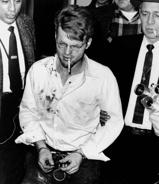 A cigarette dangles from the mouth of handcuffed killer Charles Starkweather as he is led into the Nebraska penitentiary by Sheriff Merle Karnopp, right, of Lincoln on February 1, 1958.  Bloodstains on the shirt are from minor wounds suffered during his Wyoming capture. (Photo by Don Ultang/AP Photo)