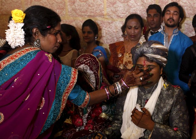 A groom receives a dot on his forehead with Sindoor (red pigment) during a mass marriage ceremony in Karachi, Pakistan, January 24, 2016. (Photo by Akhtar Soomro/Reuters)