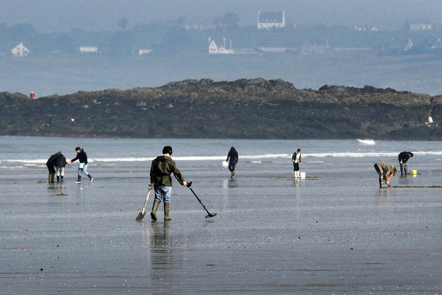 """People dig for shellfish while another uses a metal-detector during a record low tide on Kerlaz beach near Douarnenez in western France, March 21, 2015. Parts of the French coast will be on alert for the so-called """"tide of the century"""", with a tidal coefficients of 119 out of a maximum of 120 today. (Photo by Mal Langsdon/Reuters)"""