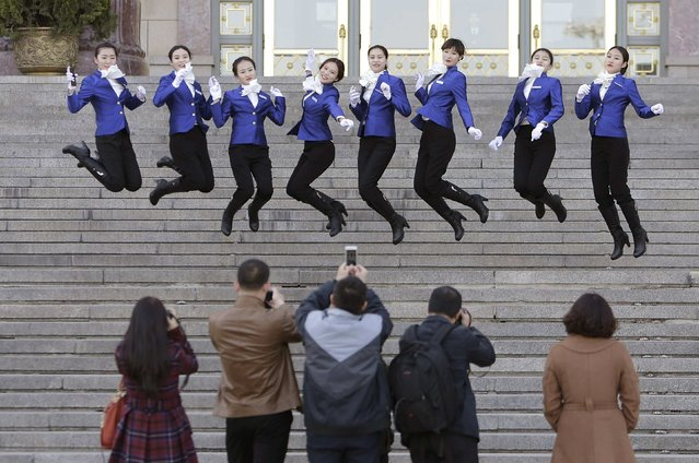 Hotel guides (top) jump as they pose for photographs on the stairs during the closing session of the Chinese People's Political Consultative Conference (CPPCC) outside the Great Hall of the People, in Beijing, March 13, 2015. (Photo by Jason Lee/Reuters)