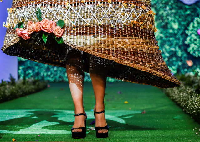 A model presents a creation by Colombian designer Laura Campo made with organic elements during BioFashion Show, on November 17, 2018, in Cali, Valle del Cauca department, Colombia. BioFashion is an environmental initiative that seeks to create awareness about the preservation and management of natural resources where new designers develop dresses made with living plants, flowers and organic elements. (Photo by Luis Robayo/AFP Photo)