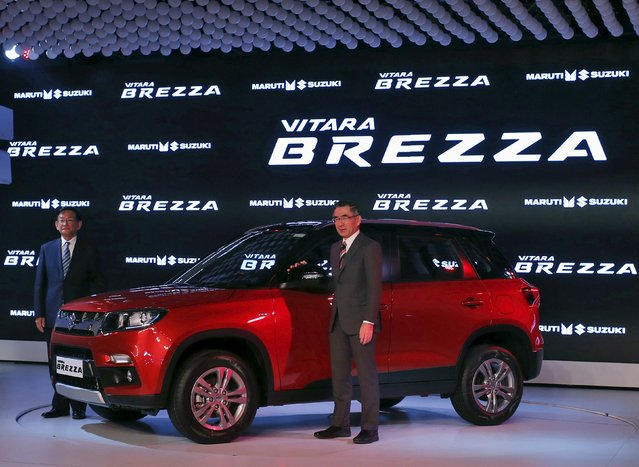 Suzuki Motor's President Toshihiro Suzuki (R) and Kenichi Ayukawa, Managing Director and CEO of Maruti Suzuki India Ltd., pose with their newly launched Brezza car during the Indian Auto Expo in Greater Noida, on the outskirts of New Delhi, India, February 3, 2016. (Photo by Anindito Mukherjee/Reuters)