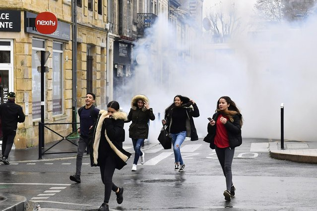 High school students run away from tear gas during a demonstration against French government Education reforms on December 3, 2018 in Bordeaux, southwestern France. (Photo by Nicolas Tucat/AFP Photo)