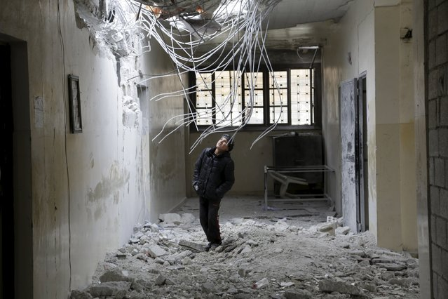 A boy inspects damage inside his school, due to what activists said was an air strike carried out yesterday by the Russian air force in Injara town, Aleppo countryside, Syria January 12, 2016. (Photo by Khalil Ashawi/Reuters)