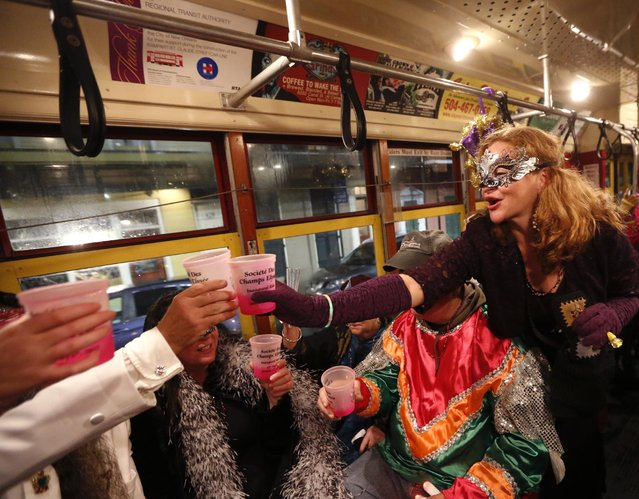"""Members of the """"Societe des Champs Elysee"""" toast as they ride the Rampart-St. Claude street car line, which just opened last fall, to commemorate the official start of Mardi Gras season, in New Orleans, Friday, January 6, 2017. (Photo by Gerald Herbert/AP Photo)"""