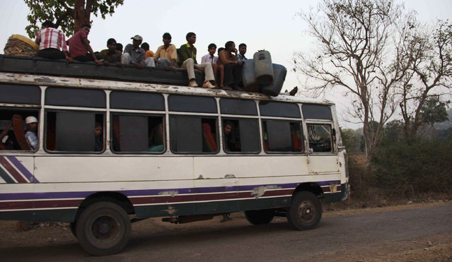 Tribal villagers sit atop of a bus as they travel through the remote district of Kandhamal in Odisha March 18, 2012. (Photo by Reuters/Stringer)