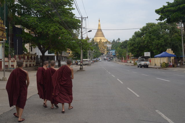 Young Buddhist monks walk on a road leading to the Shwedagon Pagoda in Yangon, Myanmar Friday, April 16, 2021. Opponents of Myanmar's ruling junta went on the political offensive Friday, declaring they have formed an interim National Unity Government comprising elements of the ousted government of Aung San Suu Kyi as well as prominent members of major ethnic minority groups. (Photo by AP Photo/Stringer)