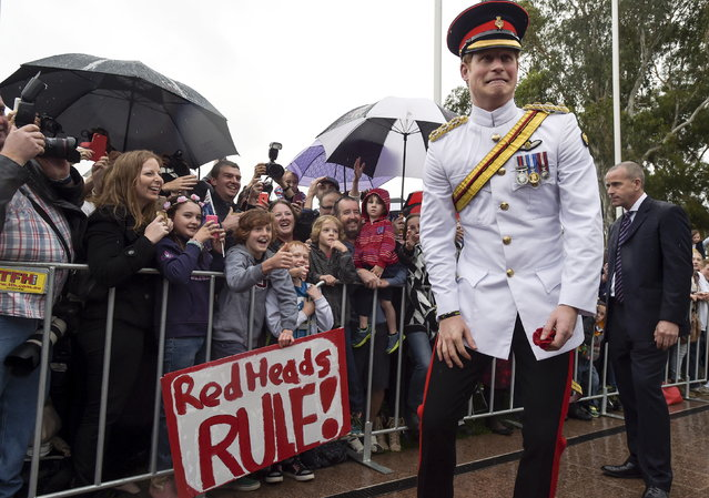 Britain's Prince Harry reacts as he shakes hands with members of the public displaying a sign reading 'Red Heads Rule' after visiting the Australian War Memorial in Canberra April 6, 2015. (Photo by Lukas Coch/Reuters)