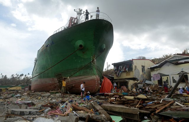 People walk amongst debris next to a ship washed ashore in the aftermath of Super Typhoon Haiyan at Anibong in Tacloban, eastern island of Leyte on November 11, 2013. (Photo by Noel Celisnoel Celis/AFP Photo)