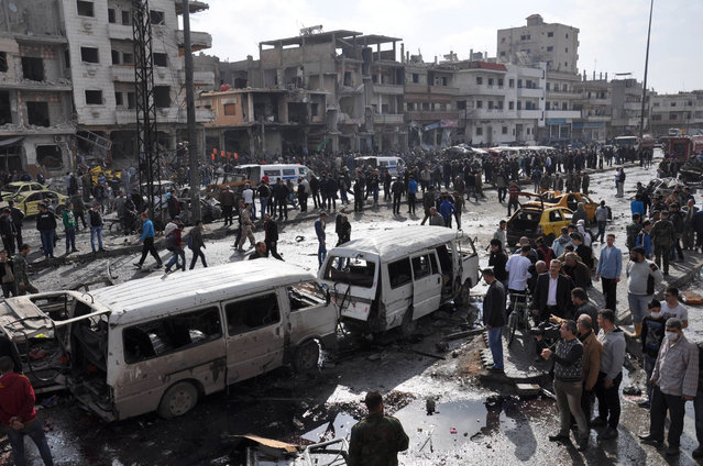 Syrians gather at the site of a double car bomb attack in the Al-Zahraa neighbourhood of the central Syrian city of Homs on February 21, 2016. Homs city is almost completely controlled by the Syrian government, and has regularly been targeted in bomb attacks. (Photo by AFP Photo/Stringer)