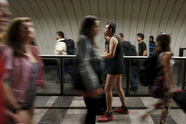 """A passenger stands without pants inside the subway as people walk pass during the """"No Pants Subway Ride"""" in Mexico City, Mexico, February 21, 2016. (Photo by Carlos Jasso/Reuters)"""