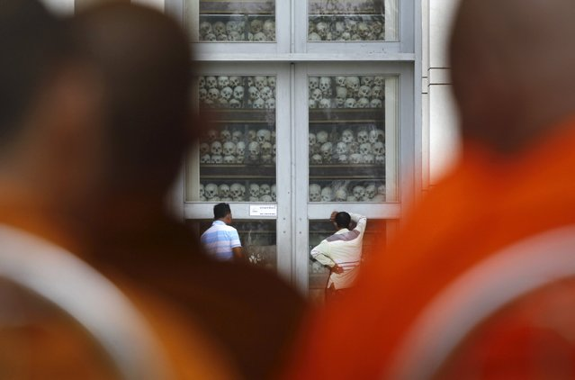 """Men look at skulls and bones of more than 8,000 victims of the Khmer Rouge regime during a Buddhist ceremony at Choeung Ek, a """"Killing Fields"""" site located on the outskirts of Phnom Penh, April 17, 2015. (Photo by Samrang Pring/Reuters)"""